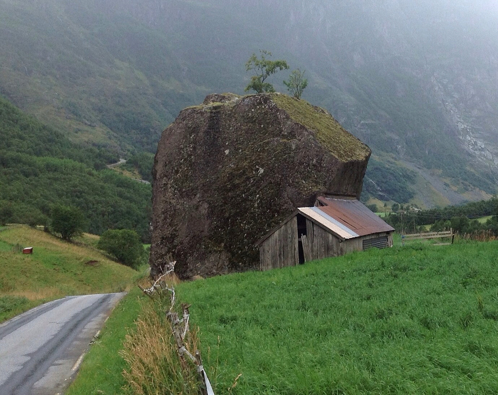Photo: Nick/Flickr | A cottage house attached to a gigantic rock.