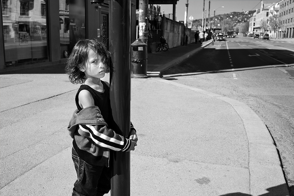 A small boy in Oslo embracing traffic light pole. His facial expression is striking. | Photo: H.K. Nilsen
